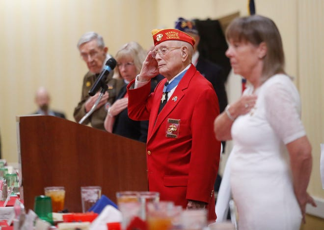 """Medal Of Honor recipient Hershel """"Woody"""" Williams salutes the flag during the National Anthem at the For Love of Country and Freedom dinner at the MCM Elegante Thursday, August 12, 2021."""