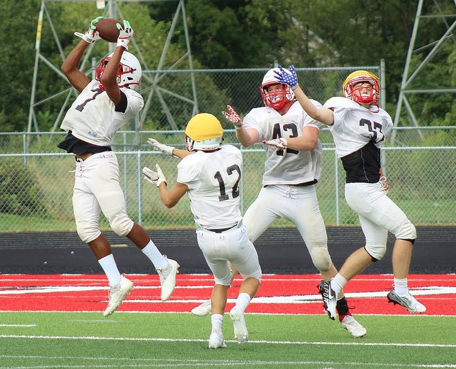 New Boston Huron senior Matthew Williams (left) comes back to make a nice catch during offensive drills at practice.