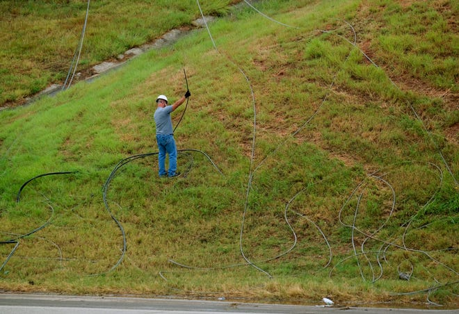 A utility worker surveys the cable after it was removed from the roadway. A storm that went through the Oklahoma City metro snapped utility poles along Memorial Rd and caused the lines to fall across I-35, closing down the highway in both directions, until the lines were cleared Friday afternoon, August 13, 2021.
