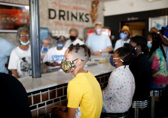Jherimyah Cross, 12, sits at the counter at Kaiser's Grateful Bean Cafe during a reenactment Saturday of the 1958 sit-in at Katz Drug Store in Oklahoma City. Pictured behind the counter are members of the Oklahoma City Sit-inners.