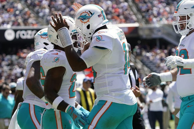 Dolphins running back Salvon Ahmed (26) celebrates his touchdown catch with the man who threw it, quarterback Jacoby Brissett, during the first half of Saturday's game against the Bears.