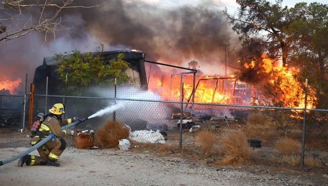 Firefighter trains hose on flames burnnig through a 2.5 acre lot Friday night.