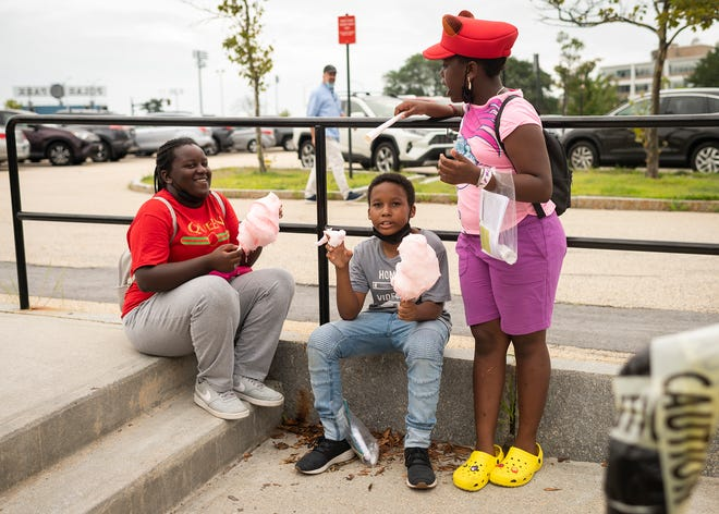 Mikay Baptist, 13, Intence Arthur, 11, and Shanelle Baptist, 9, enjoy cotton candy during the Worcester Public Library community block party on Saturday.