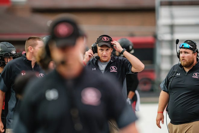 New Philadelphia head coach Mike Johnson readjusts his headset during the Quakers scrimmage against Green High School Aug. 13 at Woody Hayes Quaker Stadium.