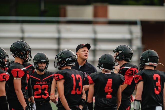 New Philadelphia Football Head Coach Mike Johnson talks with the offensive line during the team's scrimmage against Green High School, Friday, August 13 at Woody Hayes Quaker Stadium.