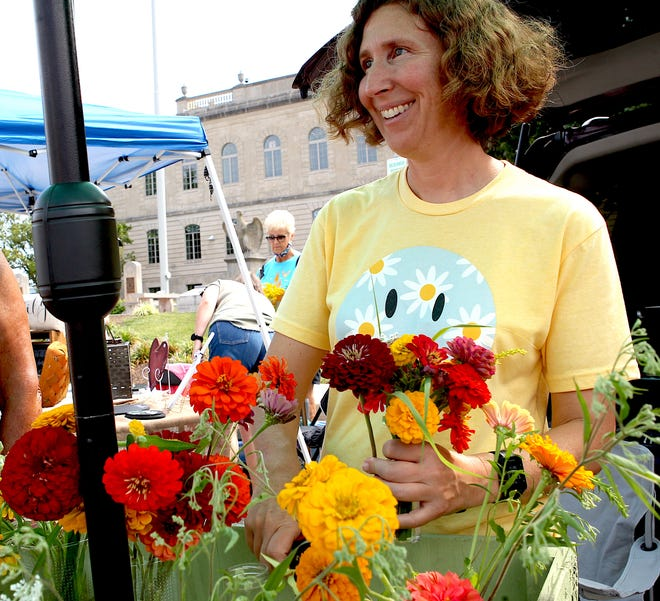 Fresh Flowers Market vendor Amy Spence talks with a customer Saturday morning.