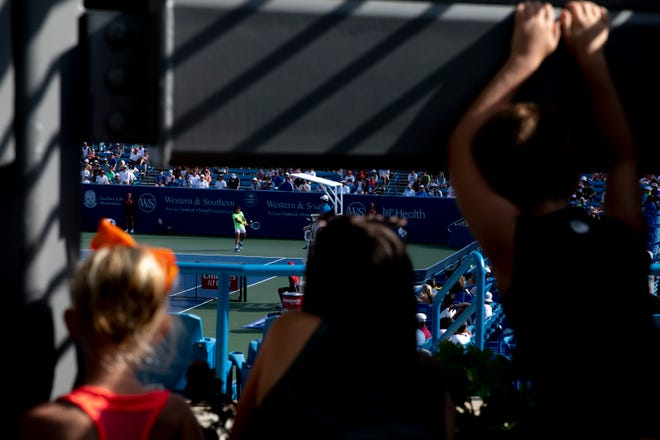 Fans watch J.J. Wolf hits a backhand return to Marcos Giron during their match at the Western Southern Open tennis tournament on Saturday, Aug. 14, 2021 in Mason, Ohio.