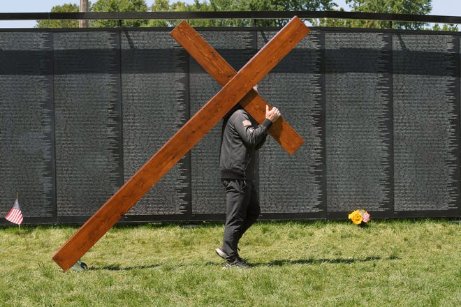 """Dan Beazley of Northville said he was """"moved by the Lord"""" to carry a crucifix and pay his respects at the sight of the Vietnam Veterans Memorial replica."""