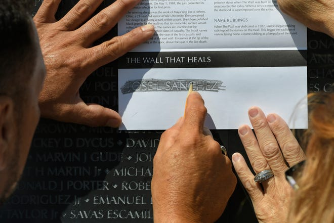 Alberto Sanchez of Melvindale, left, with the help of fiancee Kelli Norton, uses pencil and paper to make a rubbing of the name of his dad's cousin, Jose L. Sanchez, who died in Vietnam on June 1, 1969.