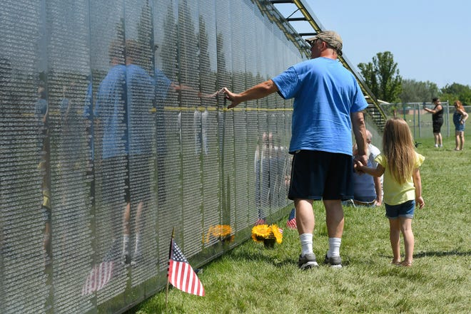 Rob Lakomy of Wyandotte holds the hand of his granddaughter, October Liska, as they look over a three-quarter scale replica of the Vietnam Veterans Memorial on Saturday, Aug. 14, 2021 in Riverview, Michigan.