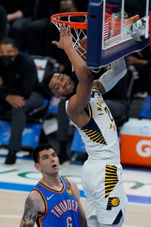 Indiana Pacers guard Cassius Stanley, right dunks in front of Oklahoma City Thunder forward Gabriel Deck, left, in the second half of an NBA basketball game Saturday, May 1, 2021, in Oklahoma City. (AP Photo/Sue Ogrocki)