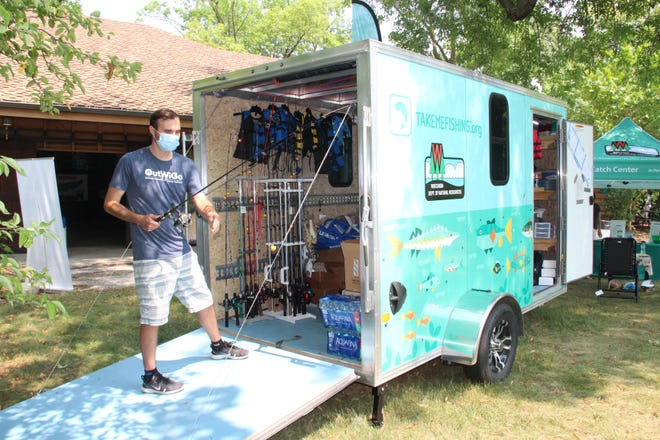 Andrew Krismer, angler R3 coordinator with the Department of Natural Resources, arranges tackle in the department's new Fishmobile on display at the Wisconsin State Fair.