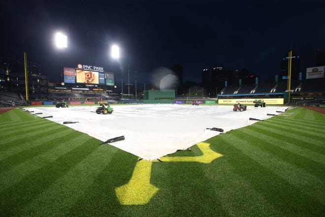 The tarp sits on the infield Friday night at PNC Park, where the Brewers-Pirates game was rained out.