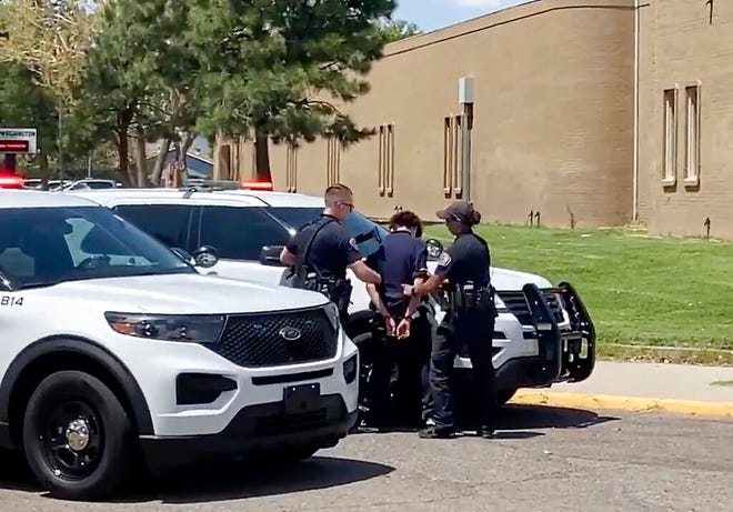In this image from taken from video courtesy of Ryan Laughlin/KOB 4 TV Albuquerque Police Department officers search a student after a shooting at Washington Middle School which left at least one student dead and another in custody, police said Friday, Aug. 13, 2021.