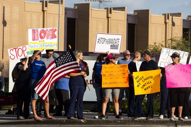 Anti-vaccine protesters gather outside Phoenix Children's Hospital in Phoenix on Aug. 13, 2021.