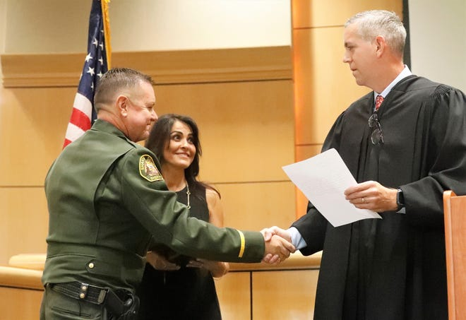 Shasta County Superior Court Judge Jody Burgess, right, shakes hands with new Shasta County Sheriff Michael Johnson after he was sworn in Friday, Aug. 13, 2021, in the Board of Supervisors chambers. Looking on is Johnson's wife, Rosemary.