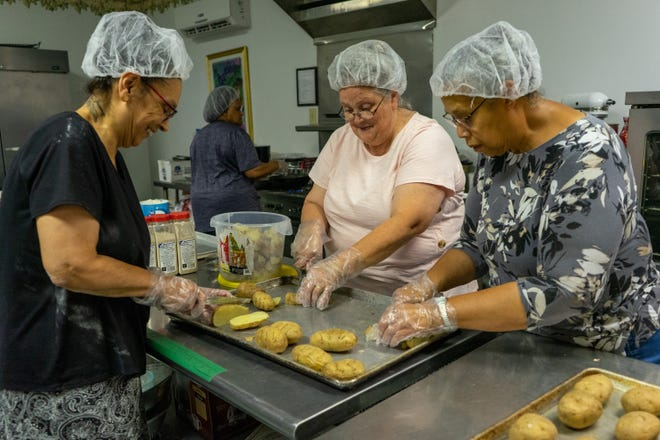 Twila Norman, Diana Anderson and Margaret Anderson (from left) slice potatoes that will be used for home fries at the fair.