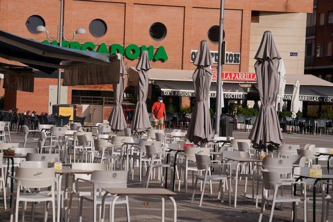Un uomo passa davanti a tavoli e sedie vuoti sotto il sole cocente fuori da un bar a Madrid, in Spagna, sabato 14 agosto 2021. La Spagna ha subito la giornata più calda sabato, con temperature superiori a 115 gradi Fahrenheit.  (Foto AP/Paul White)