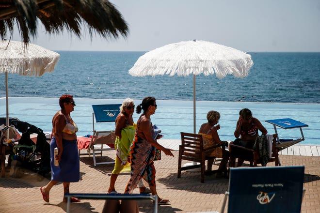 Le persone si divertono a camminare lungo la spiaggia, a Ostia, in Italia, sabato 14 agosto 2021. Le autorità italiane hanno espresso preoccupazione per gli anziani e altre persone a rischio, estendendo l'allerta per il caldo a 16 città.  (Cecilia Fabiano/La Presse via The Associated Press)