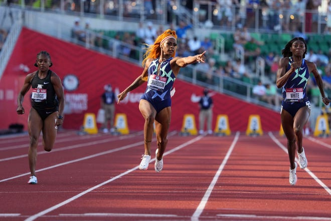 Sha'Carri Richardson (center) celebrates after defeating Cambria Sturgis (left) and Kayla White to win a women's 100-meter semifinal in a wind-aided 10.64 during the US Olympic Team Trials at Hayward Field.