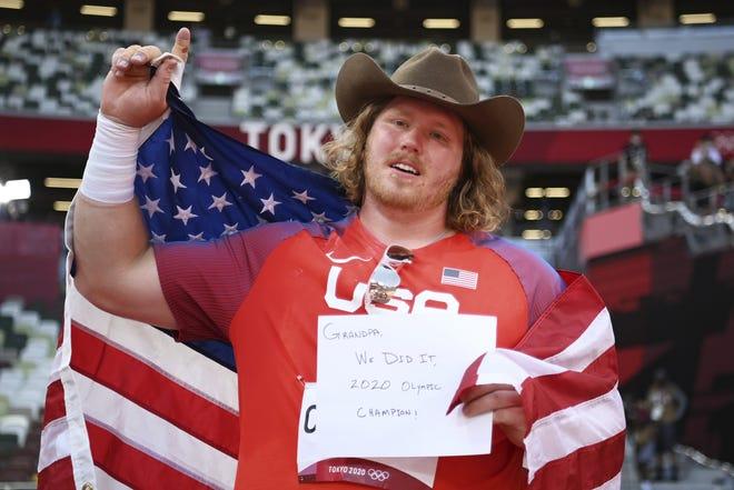 """米国の砲丸ができライアンクラウザー(Ryan Crouser)が東京五輪男子砲丸投げ金メダルを獲得した後、祖父を称える立て札を持っている。 彼の祖父であるLarry CrouserはCrouserが日本に発つ日前に死亡しました。 """"おじいちゃん、"""" 標識が読んで、 """"私たちはそれをやった。"""""""