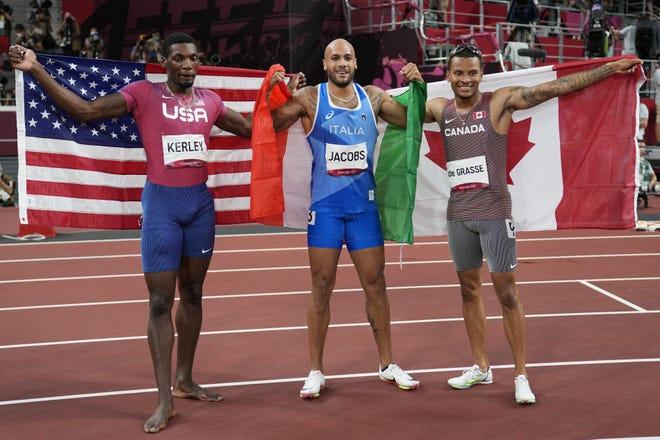 イタリアラモンマルセル・ジェイコブス(中央)が東京夏季五輪男子100m決勝後の銀メダリスト、米国フレッド・カーリー(Fred Kerley)、銅メダルリストアンドレ・デ・グラス(Canada)(右)と一緒に記念撮影をしている。  JacobsとKerleyは、それぞれEl PasoとTaylorで生まれました。