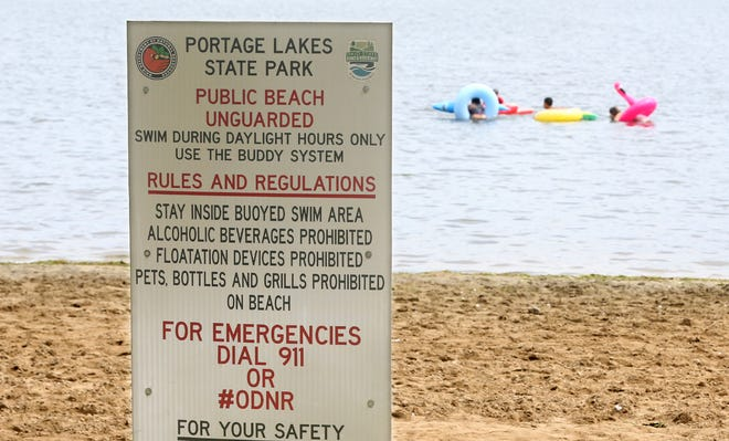 A caution sign is shown as children swim in the background Sunday at the Portage Lakes State Park beach in New Franklin,  where an 11-year-old boy drowned Saturday.