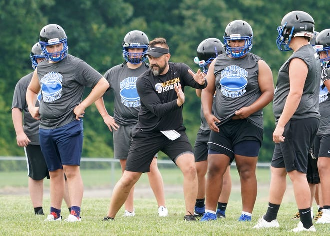 Madison head football coach Scott Gallagher works with the lineman during a practice.