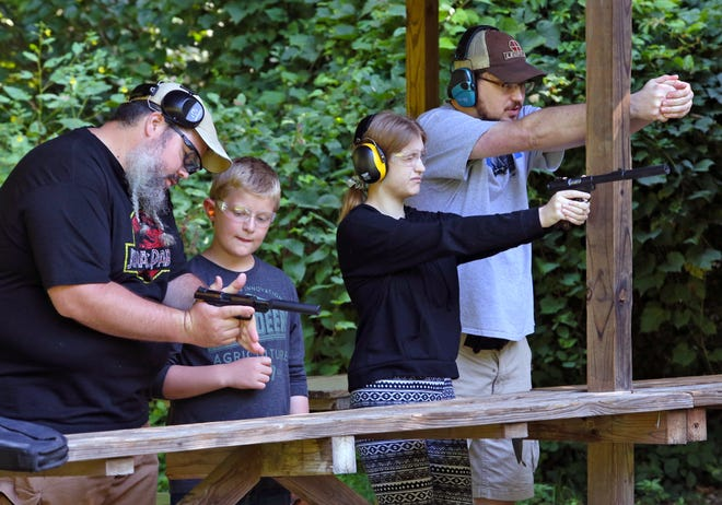 Clayton Thoroughman, 11, left, of Garden City is instructed by Jeremy Piar, and, third from left, Evelyn Bowe, 17, of Blissfield practices aiming with the help of instructor James Garrison Saturday at the Lenawee County Conservation League. They were taking part in an event at which Republicans thanked youth for their help with getting out the vote in 2020.