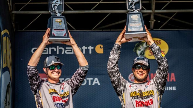 Adrian College's Hayden Scott and Griffin Fernandes hold up their trophies after winning the 2021 Carhartt Bassmaster College Series National Championship presented by Bass Pro Shops at the St. Lawrence River in Waddington, New York.