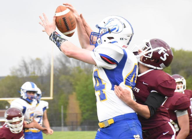 Mt. Markham Mustang Logan Clark (44) attempts a leaping catch May 7 with Dominick Scialdo defending for Frankfort-Schuyler during both teams' final Fall II football game this spring. Current plans have practice for a return to a traditional fall schedule starting next week.