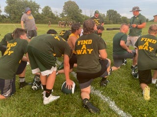 """Flat Rock football players, many wearing shirts with the logo """"Find A Way"""", kneel to hear coach Buck Reaume talk."""
