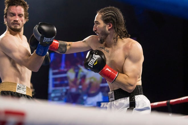 Nico Ali Walsh, right, lands a punch to Jordan Weeks' jaw during a middleweight bout on Saturday in Tulsa. Walsh is the grandson of boxing legend Muhammad Ali.