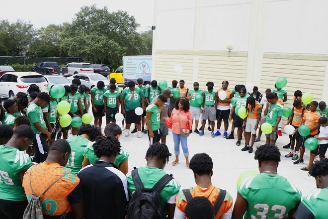 The Eagles circle around senior cornerback Jekkaven Smith and head coach Jamael Stewart on Saturday as the new principal of Atlantic High, Sandra Edwards, leads the team in prayer.