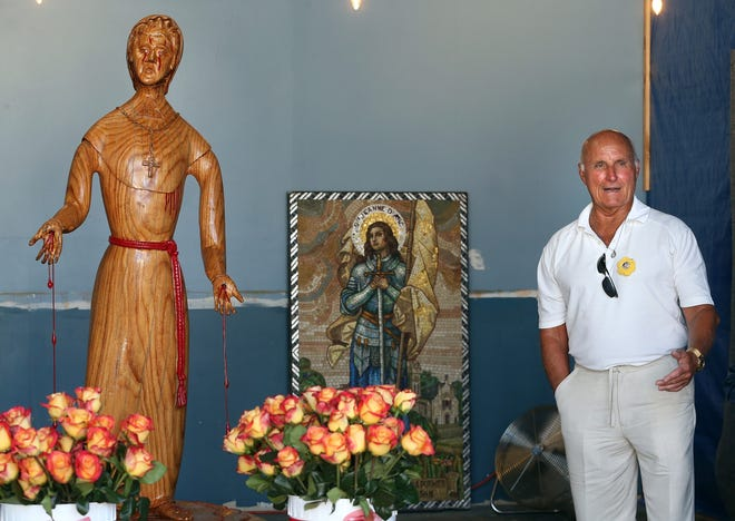 Artist Ed Goodhart of North Providence stands next to the statue of Marie Rose Ferron that he carved and donated to the Rose Ferron Foundation of Rhode Island.