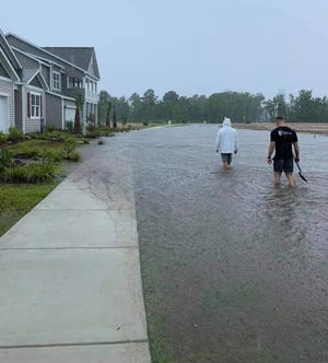 Residents walk through floodwaters up to their knees in a housing community developed by D.R. Horton.