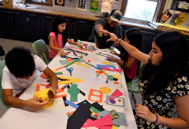 Jonathon Cortez (center) passes a bucket of supplies to his daughter Jayla, 14, during the Make-and-Take art activity at The Grace Museum on Thursday.