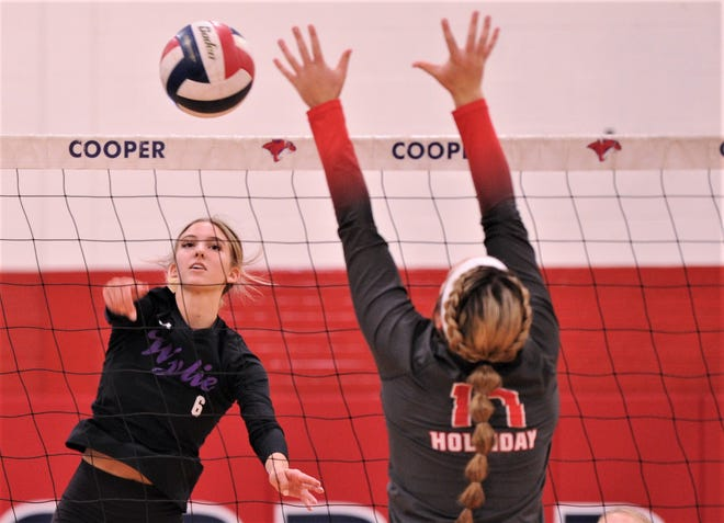 Wylie's Jaron McAden, left, hits the ball past Holliday's Campbell Jurecek during their second-round match at the Bev Ball Classic on Saturday at Cooper's Cougar Gym. Holliday won 23-25, 26-24, 25-19.