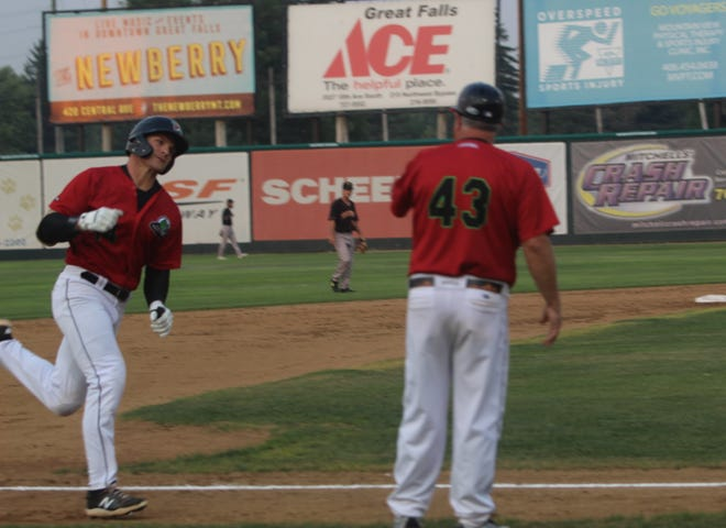 Voyagers manager Tommy Thompson greets Michael Deeb after the left fielder belted a solo home run in the second inning against Missoula Saturday night at Centene Stadium