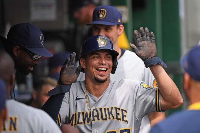 PITTSBURGH, PA - AUGUST 15: Willy Adames #27 of the Milwaukee Brewers celebrates with teammates in the dugout after coming around to score on a RBI single by Eduardo Escobar #5 in the first inning during the game against the Pittsburgh Pirates at PNC Park on August 15, 2021 in Pittsburgh, Pennsylvania. (Photo by Justin Berl/Getty Images)