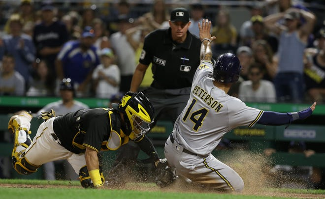 Brewers first baseman Jace Peterson scores past Pirates catcher Michael Perez on Saturday night, advancing from second base after a throwing error by Perez on a pick-off attempt in the second game of the teams' doubleheader.