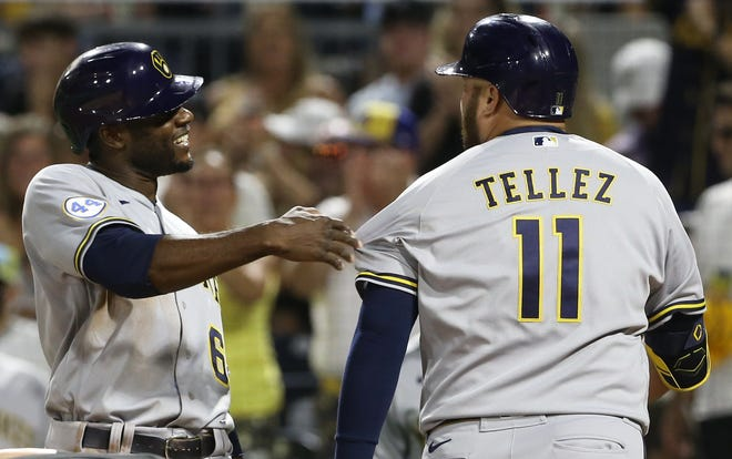 Brewers centerfielder Lorenzo Cain congratulates pinch-hitter Rowdy Tellez on his two-run homer against the Pirates during the sixth inning of Game 2 of their doubleheader Saturday.