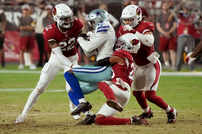 Dallas Cowboys wide receiver Malik Turner is tackled by Arizona Cardinals cornerback Marco Wilson as safety Deionte Thompson (22) and linebacker Zeke Turner, right defend during the first half of an NFL preseason football game, Friday, Aug. 13, 2021, in Glendale, Ariz. (AP Photo/Rick Scuteri)