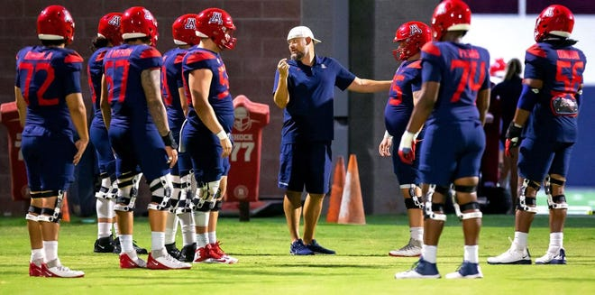 Arizona offensive coordinator and offensive line coach Brennan Carroll, center, talks with his players during a practice earlier this month.