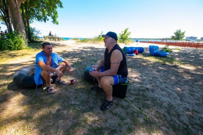Brandon Segnitz and Lorny Miller, both of Kimball, sit on their intertubes near the beach before Float Down at Lighthouse Beach in Port Huron.