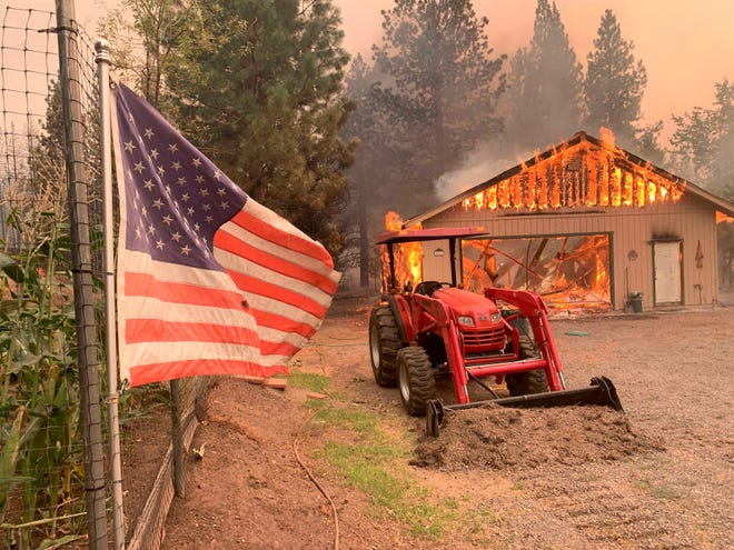 """A red tractor is left behind as a home burns outside of Taylorsville in Plumas County on Friday, Aug. 13, 2021. The U.S. Forest Service said Friday it's operating in crisis mode, fully deploying firefighters and maxing out its support system as wildfires continue to break out across the U.S. West. The agency says it has more than twice the number of firefighters working on the ground than at this point a year ago, and is facing """"critical resources limitations."""" The Dixie Fire in Northern California is the largest of 100 large fires burning in 14 states, with dozens more burning in western Canada."""