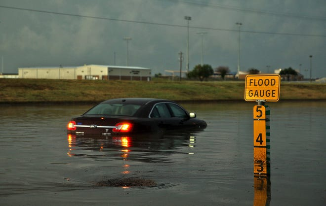 A vehicle sits submerged in over 3 feet of water on South Jackson St. near the ASU campus after a strong thunderstorm moved through the area in the early morning hours on Sunday, Aug. 15, 2021. The driver was not injured.