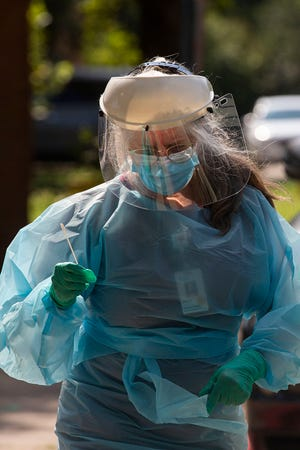 An Austin school district health care worker carries a COVID-19 sample during coronavirus testing at Cunningham Elementary School on Aug. 16. By Friday, the Austin area had surpassed a total of 102,000 coronaviruses cases since the pandemic began.