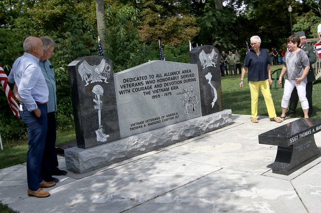 Siblings of the late Ralph E. Hunt Jr., who died in Vietnam, from left, Randy Hunt, Richard Hunt, Nancy Kile, and Martha Kucyeski, get a view of the newly unveiled Vietnam Veterans Memorial after a dedication ceremony Saturday, Aug. 14, 2021, at Memorial Park on East State Street.