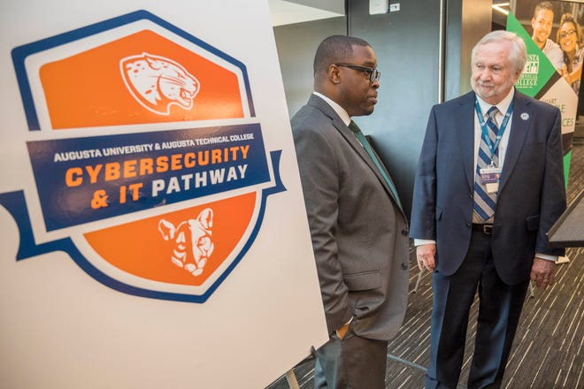 Augusta Technical College President Jermaine Whirl and Augusta University President Brooks A. Keel talk following a press conference where they announced the articulation agreement in cyber sciences on Monday at the Georgia Cyber Center.